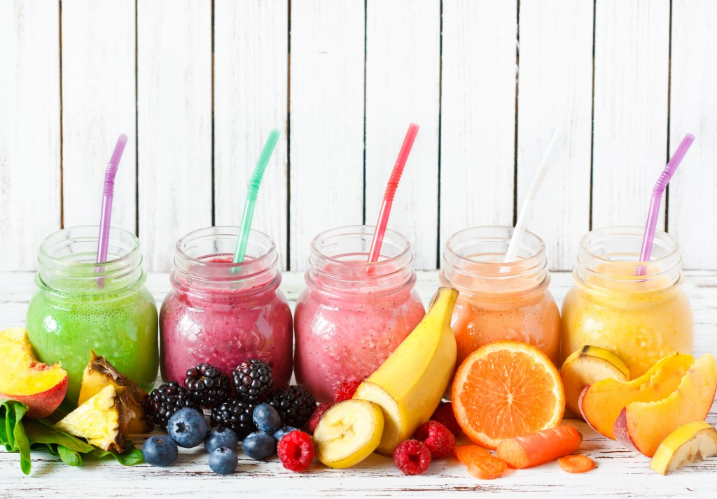 Healthy smoothies with fresh ingredients on a kitchen board.